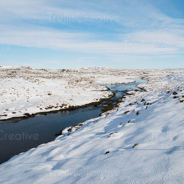 Meandering stream along snowy banks in winter