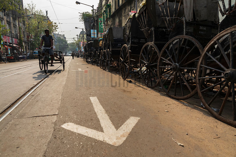 Rickshaws Lined up along the Side of a Road on a Sunday Morning