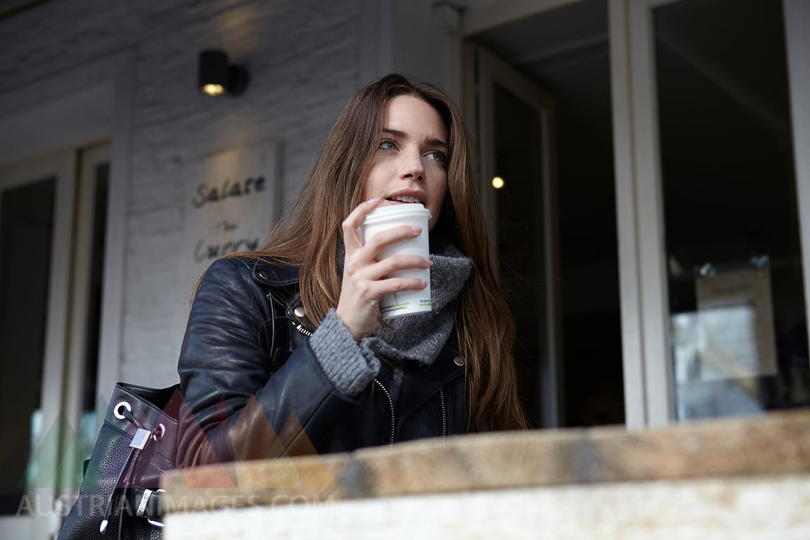 Germany, Dusseldorf, Young woman with coffee sitting outdoor