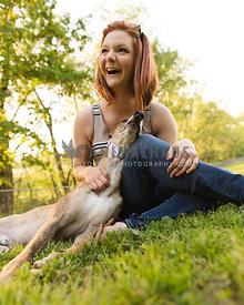 owner laughing while sitting with greyhound