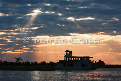 Late afternoon sun silhouetting a tourist riverboat on the River Chobe, Botswana