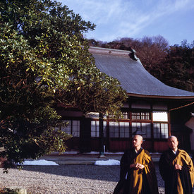 Two Buddhist monks walk in the grounds of the Seiryu-ji Temple after meditation