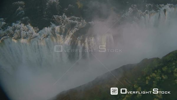 Aerial overhead wide shot looking straight down and circling top of Victoria Falls, gorge filled with mist Victoria Falls Zim...