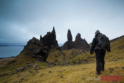 Hiker at the Old man of Storr mountain peak, Scotland, UK