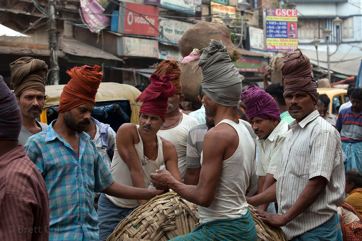 Workers unload trucks full of heavy baskets at the Kole wholesale vegetable market, Bowbazar, Kolkata, India. Kole is one of ...
