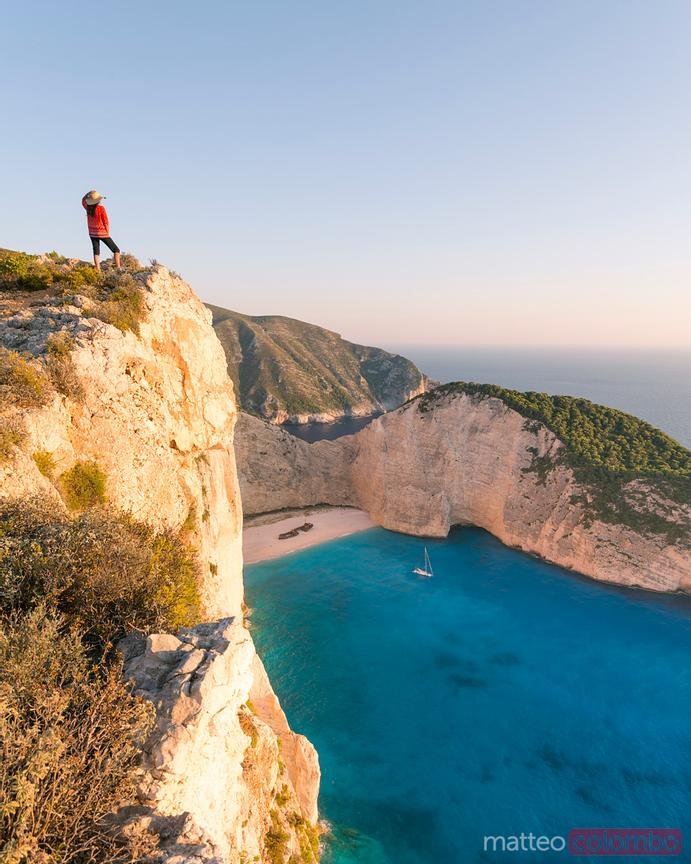 Woman standing on cliff edge over shipwreck beach. Zakynthos,  Greece