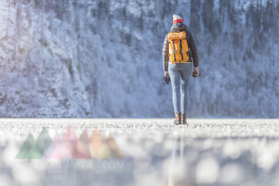 Germany, Berchtesgadener Land, back view of woman with backpack walking on frozen Lake Koenigssee