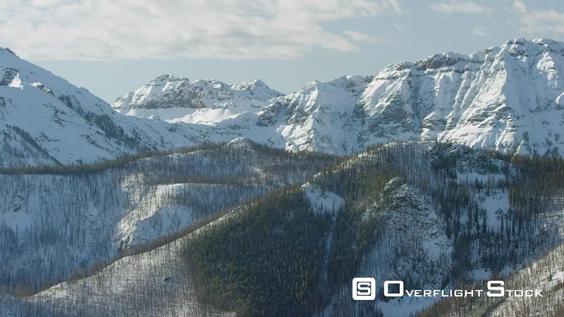 The snowcapped peaks and steep cliffs of the Absaroka mountain Range near Yellowstone National Park, and the scars of a recen...