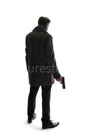 A semi-silhouette of a mystery man in a big coat, holding a gun and looking away – shot from eye level.