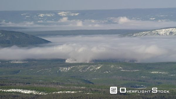 Northern forests of Yellowstone National Park, with low clouds and a small forest fire