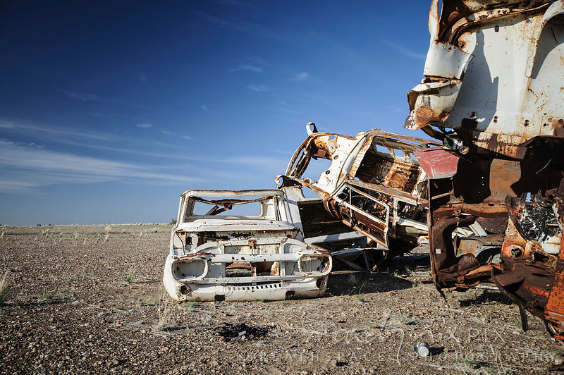 Abandoned rusted cars piled in desert
