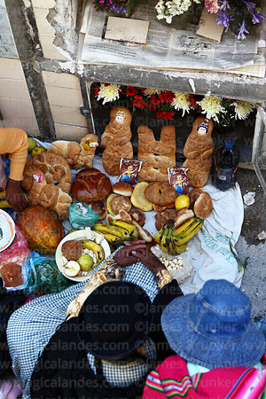 Aymara woman sitting next to tomb of deceased relative with bread offerings in cemetery during Todos Santos festival, La Paz, Bolivia