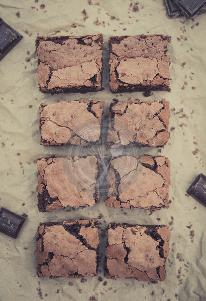 Chocolate brownies on greaseproof paper.