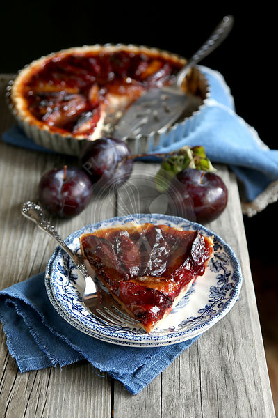 Slice of plum tart on a plate