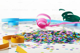 Handful of confetti surrounded with serpentines on white background
