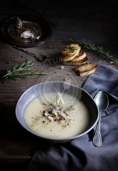 Cauliflower cream soup in bowl with grilled bread slices on wooden table