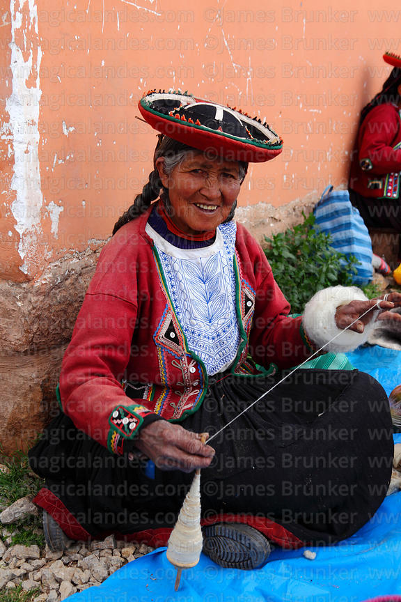 Quechua woman wearing traditional dress spinning wool at Chinchero market, Sacred Valley, Cusco Region, Peru