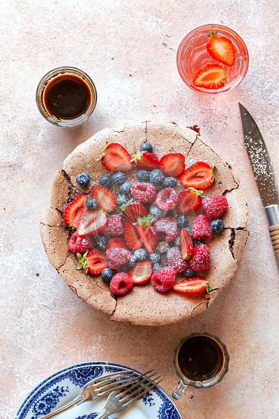Chocolate meringue cake topped with fresh fruit on the table