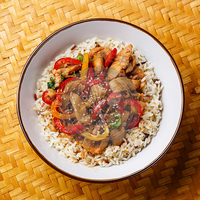 Stir-fry with chicken meat and rice in bowl on bamboo tray background close-up