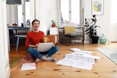 Woman sitting cross-legged on floor of her home, using laptop