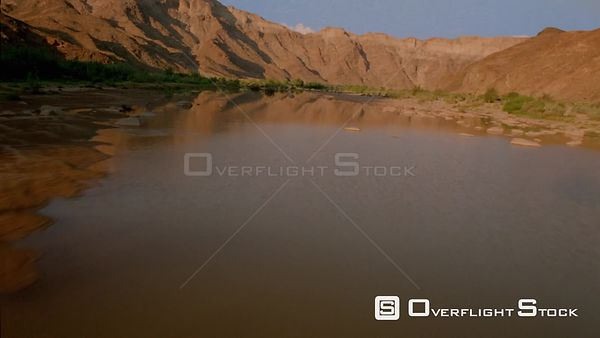 Aerial close up flying up river with mountain range reflected in water and green vegetation and stones sides of river Fish Ri...