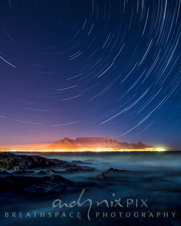 Night shot of star trails circling above Table Mountain and Cape Town viewed from Blouberg with rocks and blurred waves in th...