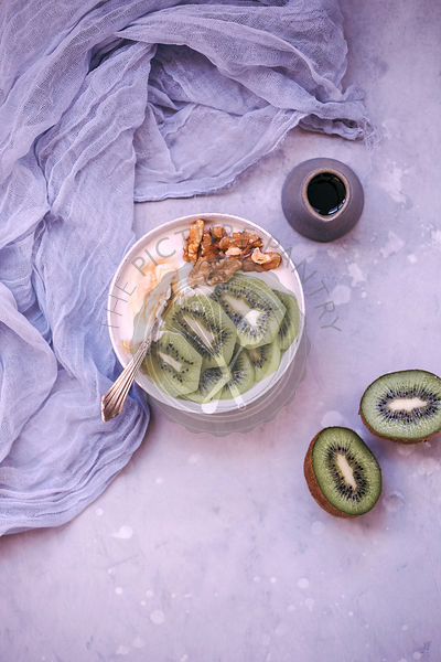 Yoghurt in a bowl topped with maple syrup, fresh kiwi and walnuts
