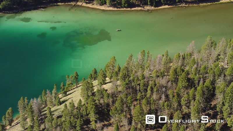 A fishing boat floats on the stunning turquoise waters of Cliff Lake in the Madison Valley of Montana