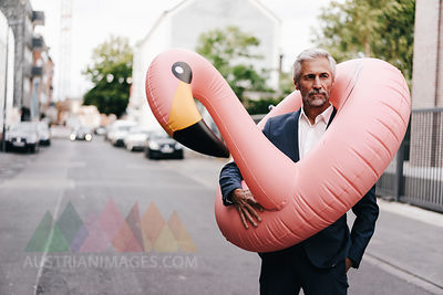 Mature businessman on the street with inflatable flamingo