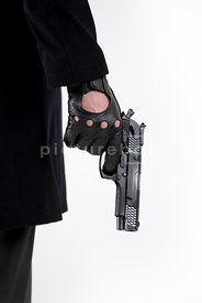 An Close-up image of a man wearing gloves and holding a gun.