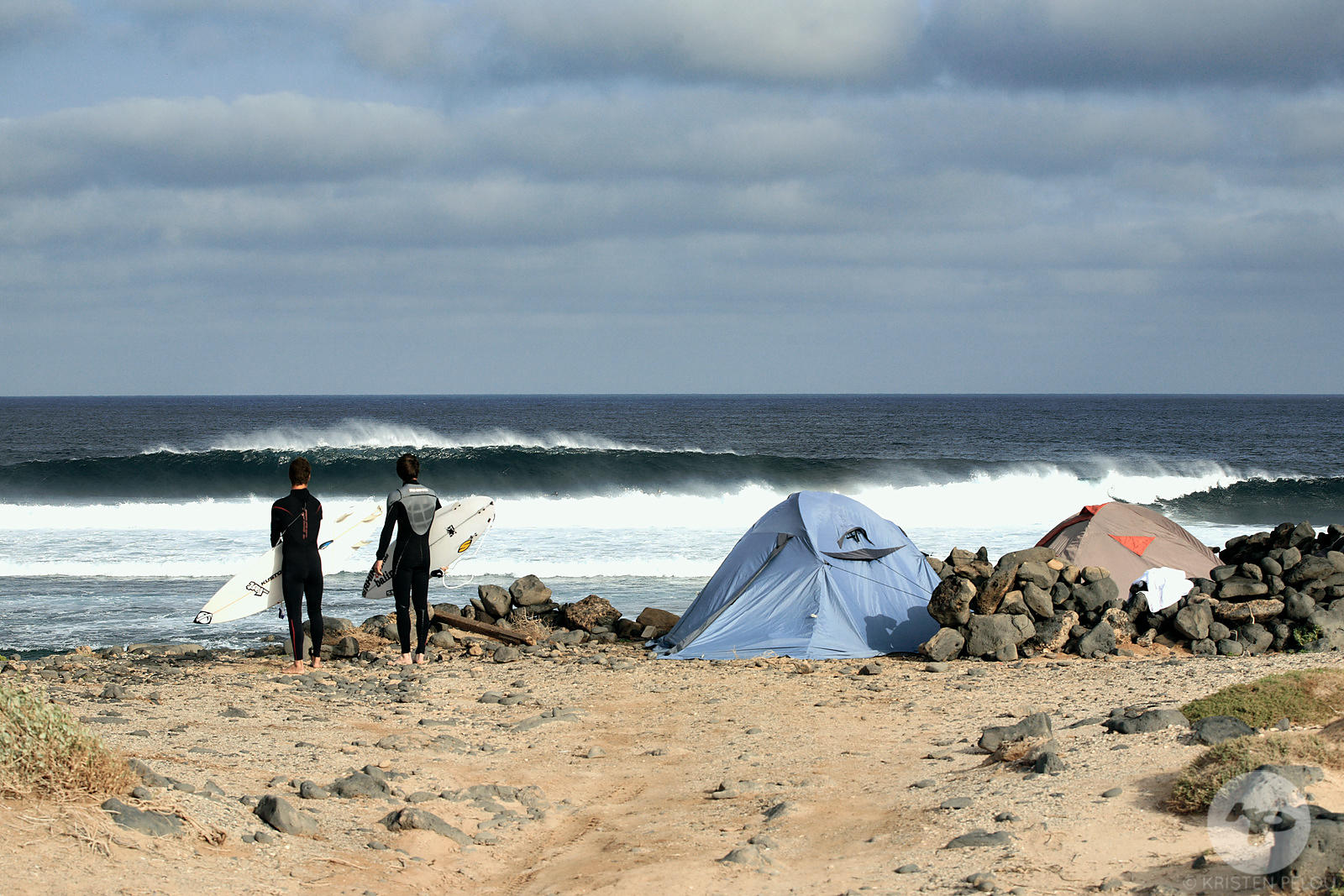 Two surfers watching a  wave breaking in front of a unauthorized campsite, La Graciosa island, Canary islands, Spain, march 2...