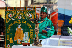 Devotee with banner and crucifix at St Peter and St Paul festival, Arica, Chile