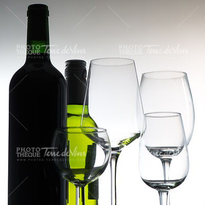 Set of wine bottles and glasses on grey background
