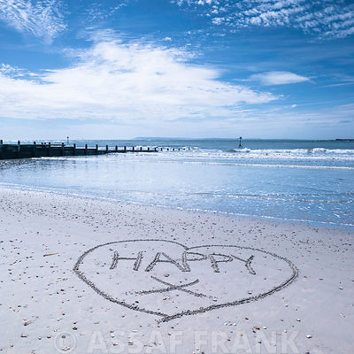 """HAPPY"" message written in big heart shape on sand at the beach"