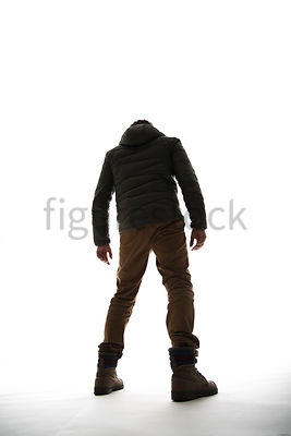 A Figurestock image of a man in outdoor clothing from behind, in silhouette – shot from low level.
