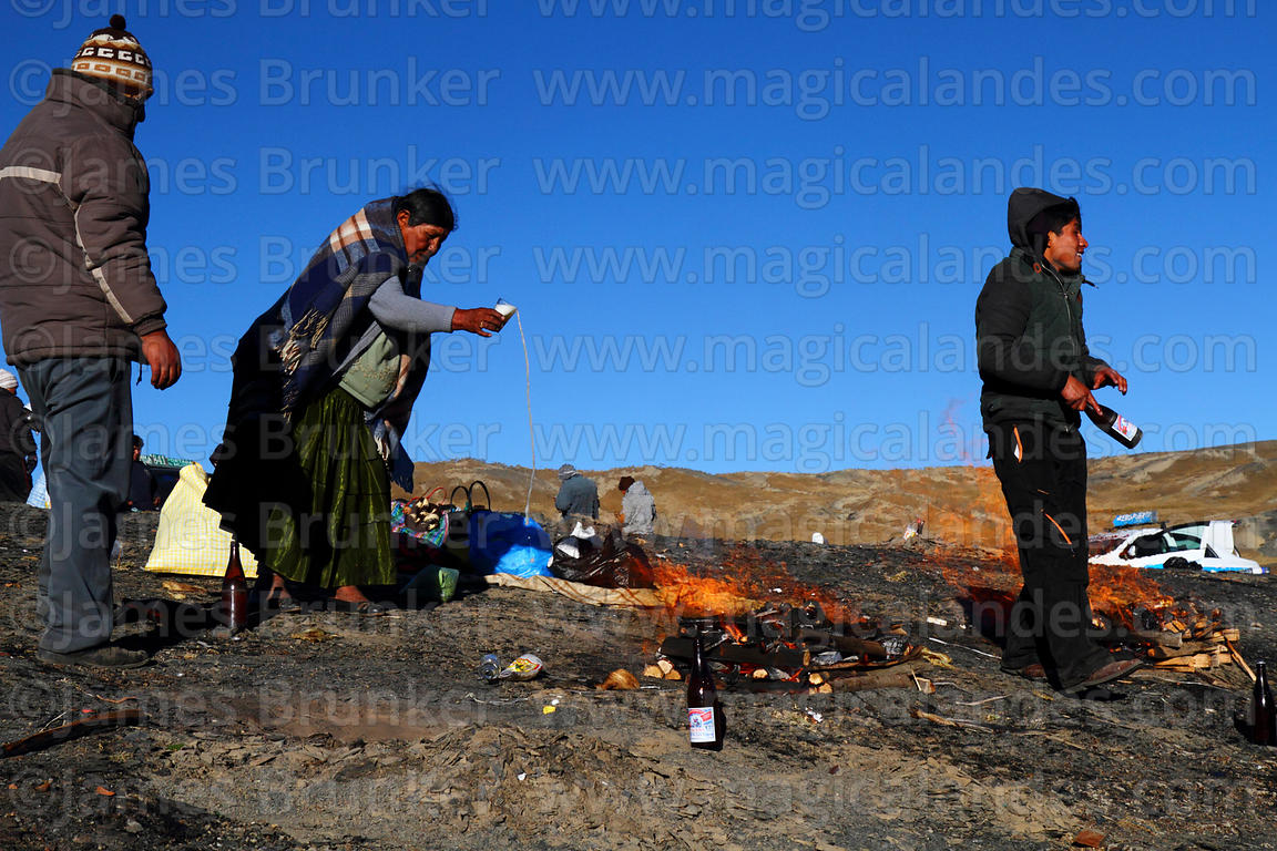 A woman pours beer on burning offerings (called k'oas) to Pachamama, La Cumbre, Cordillera Real, Bolivia