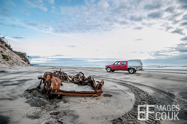 Rusted Out Car Remains On A Beach Near Strahan