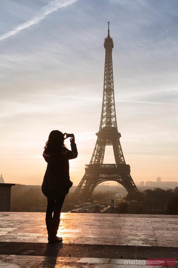Woman photographing the Eiffel tower at sunset, Paris, France