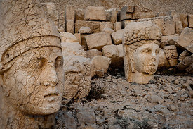 The west terrace of Mount Nemrut with heads of the colossal statues and the tumulus.  Head of Antiochos1 in foreground with C...