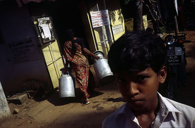 India - Kerala - A boy and his mother collect milk