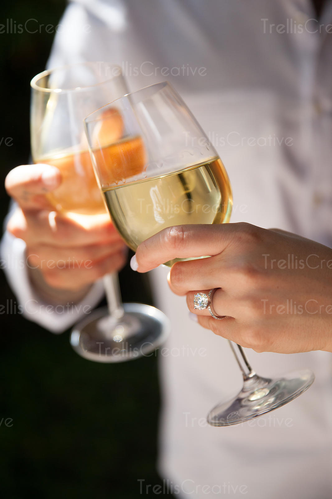 A couple toasts their engagement with white wine