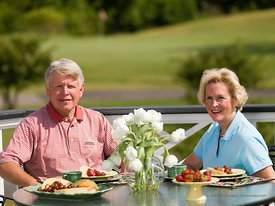 Couple with fruit setting on porch table overlooking golf course, Albemarle Plantation, Hertford, NC