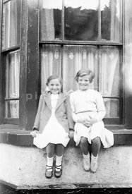 (Not for misery memoir use) An old family photograph of two girls sitting on the windowsil of an old victorian house, 1940's/...