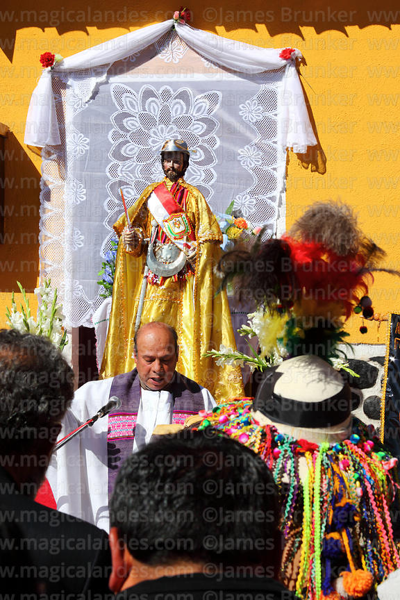 Tinku dancer standing in congregation while priest gives mass for San Bartolome at start of Chutillos festival, Potosí, Bolivia