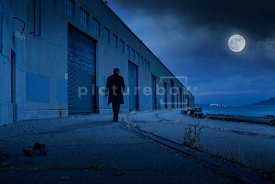 An atmospheric image of a mystery man walking along an empty industrial dock at night.