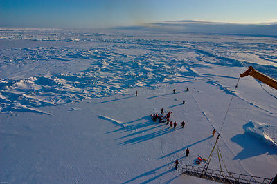 Aerial view of science teams and Frozen Planet film crew working on the sea ice in the Bering Sea, Alaska, USA, March 2008. T...