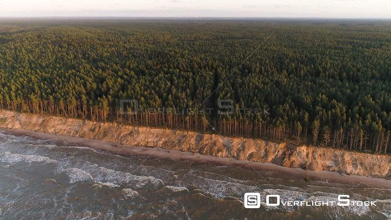 Aerial shot reveal of forest by the sea with a 4x4 off road vehicle Latvia