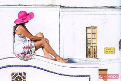 Woman seated on wall in the old town, Tarifa, Spain