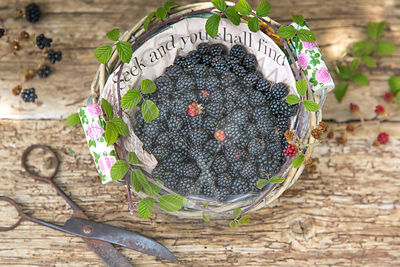 seek  and you shall find, blackberries in paper lined basket against rustic wood and vintage scissors