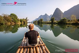 Tourists on bamboo boat on the Li river looking at karst peaks